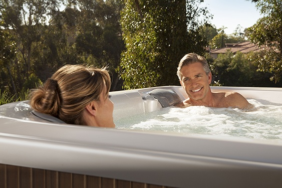 couple relaxing and enjoying a soak in a limelight flair spa with a pearl white shell and a teak colored cabinet