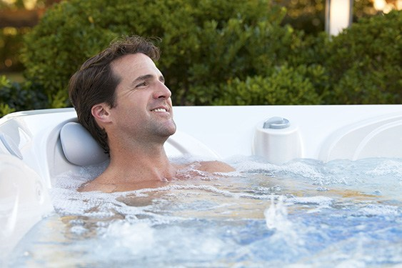 a man takes a relaxing soak in a hot spot rhythm spa on a beautiful day