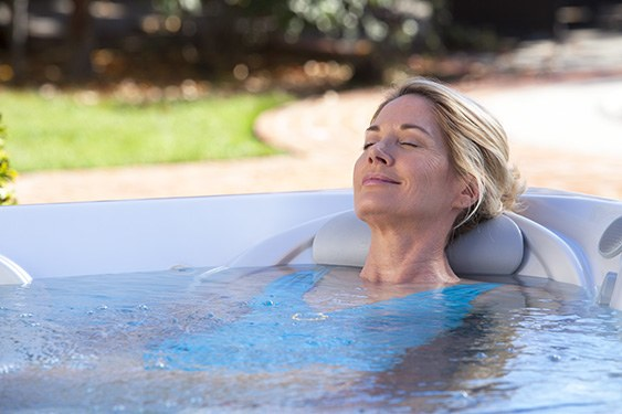 a woman takes a relaxing soak in a hot spot rhythm jacuzzi on a beautiful day